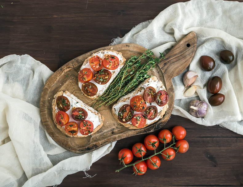 Sandwiches brushtta with roasted cherry tomatoes, soft cheese, garlic and herbs on a rustic wooden board and white kitchen towel over a dark wood background. Top view